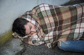 picture of beggar  - Young male beggar sleeping on city sidewalk with blanket on his shoulders - JPG