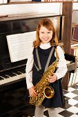 stock photo of saxophones  - Smiling girl in school uniform dress with alto saxophone standing near the piano indoors - JPG