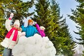 pic of snowball-fight  - Happy kids playing snowballs game together standing behind the snow wall with fir forest on the background during winter day - JPG