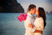 image of barefoot  - brunette bride and handsome groom barefoot kiss at sand beach at dawn - JPG