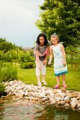 image of fish pond  - Mother with daughter feeding fish in backyard garden pond - JPG