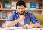 picture of draft  - Male designer dressed casual sitting at the table and drawing draft at home office - JPG