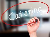 foto of catering  - Man Hand writing Catering with marker on transparent wipe board - JPG