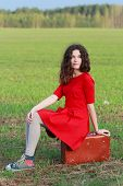 stock photo of daydreaming  - Daydreaming attractive brunette girl during her vintage travel in spring farm field - JPG
