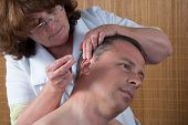 picture of pointed ears  - Woman acupuncturist prepares to tap needle around ears of man - JPG