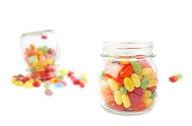 stock photo of jar jelly  - Composition of a glass jar and multiple colorful jelly bean candies - JPG
