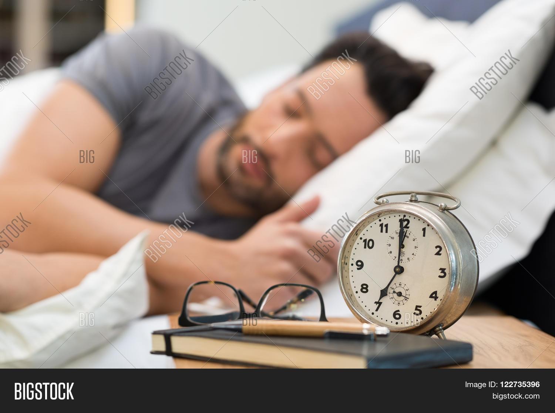 bedroom alarm clock. Young man sleeping in his bedroom  Man with an alarm clock foreground Sleeping His Bedroom Image Photo Bigstock