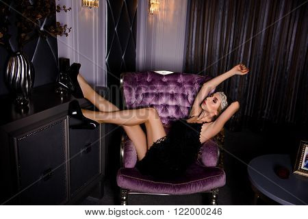 Sedutive Woman In Black Dress And High Heel Shoes Sitting On  Armchair