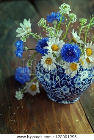 Camomile and cornflowers in a pitcher on table. Flowers from the field