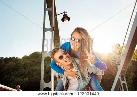 Cheerful Man Piggybacking His Girlfriend On The Bridge With Glasses