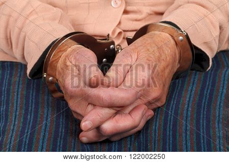 Close up photo of a handcuffed elderly woman