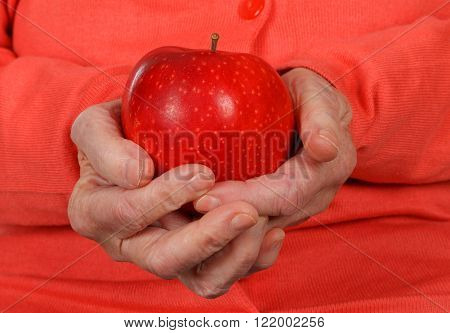 Close up photo of a senior hand holding a red apple