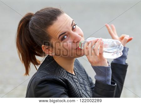 Photo of a thirsty young woman drinking water