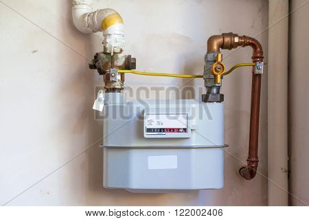 Gas meter on the white wall, industrial tools