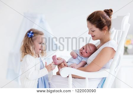 Little sister hugging her newborn brother. Toddler kid meeting new sibling. Mother and new born baby boy relax in a white bedroom. Family with children at home. Love trust and tenderness concept.