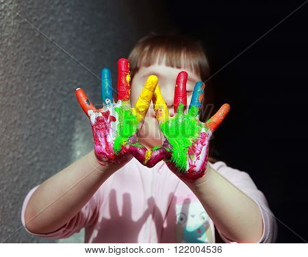 Cute little girl with a painted hands .
