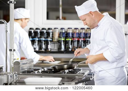 Focused chefs makes food in professional kitchen