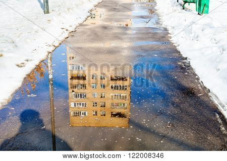 Reflection Of House In Puddle On Footpath
