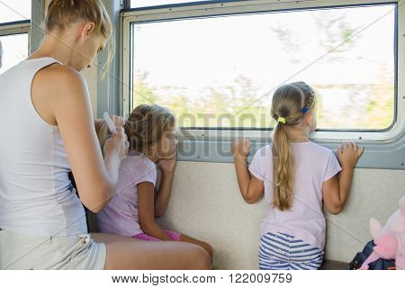 Two Girls Looking Out Of The Window While Sitting In An Electric Train Until My Mother Combs Long Ha