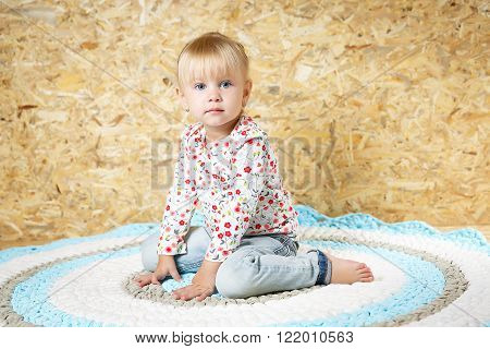 A three year old girl posing like a model in a pink room, in white blouse and pink pants with makeup red lips and a hairstyle making funny face expression