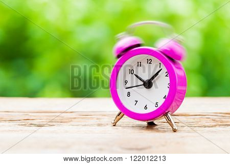Ringing pink Alarm clock on table outdoors