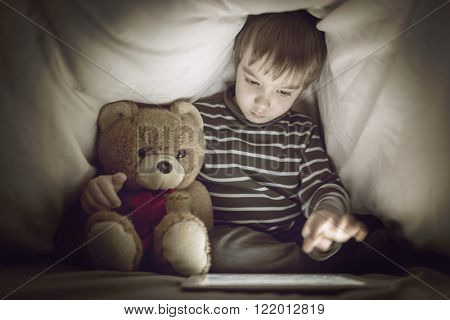 Kid under the blanket playing with tablet