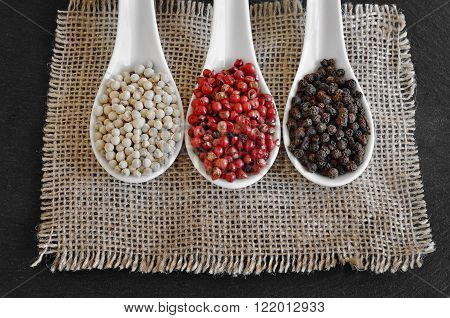 Black pepper, Piper nigrum. White pepper. Pink pepper. Different peppercorns on a rustic wooden table. Spices.