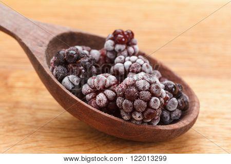Macro view frozen Blackberry fruits in spoon, wooden background