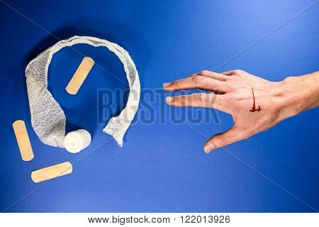 Wounded arm reach for white bandage and plaster on a blue health background