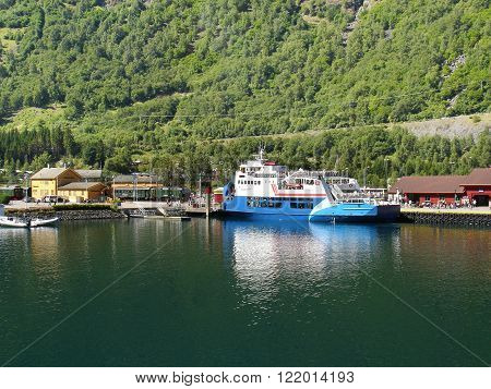 Flam, Norway - July 23, 2005: Fjord coast with ferry and electric train of famous Flamsbana railway.