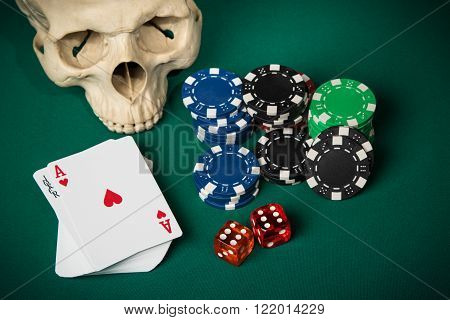 Skull, deck of cards with an ace and a joker on top, chips and dice on a green table for poker