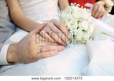 Hands of the bride and groom with rings and white wedding bouquet.