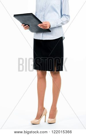 Formally dressed woman with folder. Secretary holding black leather folder. Some documents you must see. Heading to chief's office.