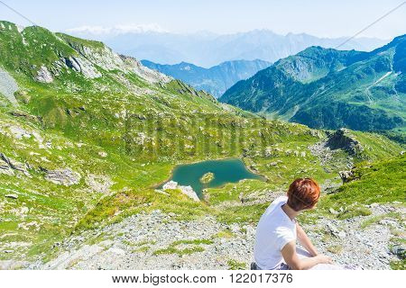 Red hair woman sitting on the mountain summit and looking at blue lake and expansive panorama of high mountain range of the Italian Alps. Summer adventures and exploration in Gran Paradiso National Park. Wide angle view from above.
