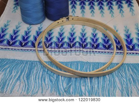 Wooden hoop for embroidery on table background with blue thread