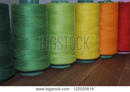 spools of thread for sewing and embroidery on the background of a wooden table