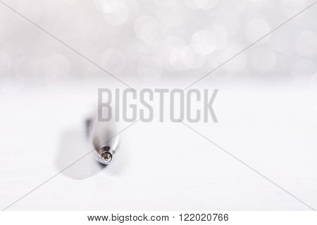 Stylish metal pen lying on white surface, on silver sparkle background. ** Note: Shallow depth of field