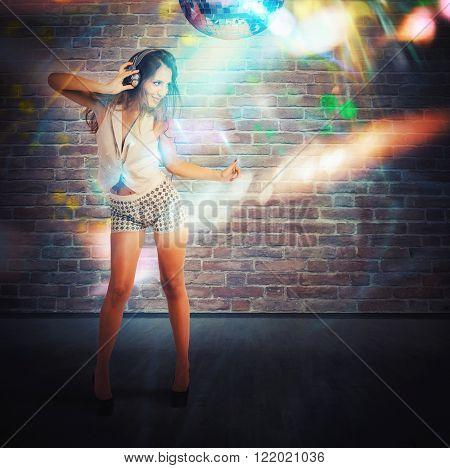 Beautiful dancing girl with headphones in nightclub