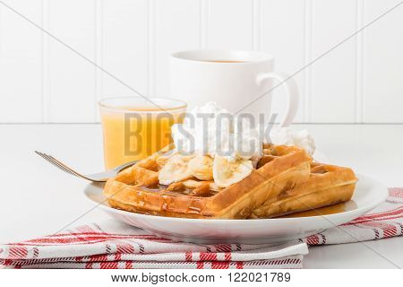 Plate of banana waffles with maple syrup and whipped cream.