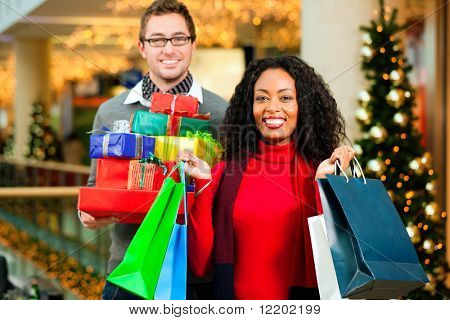 Couple - Caucasian man and black woman - with Christmas presents, gifts and shopping bags - in a mall in front of a Christmas tree