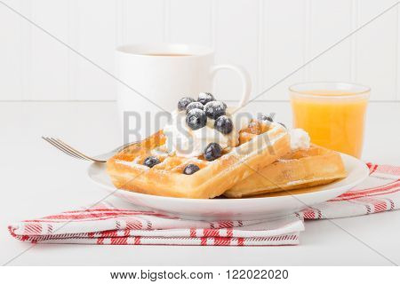 Plate of fresh waffles with blueberries coffee and juice.