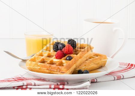 Stack of fresh waffles with maple syrup and fruit.