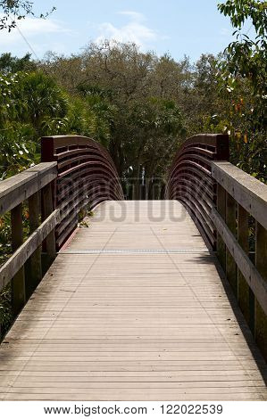 A wooden arched walking bridge with red metal side rails leads into forest in bonita springs florida.