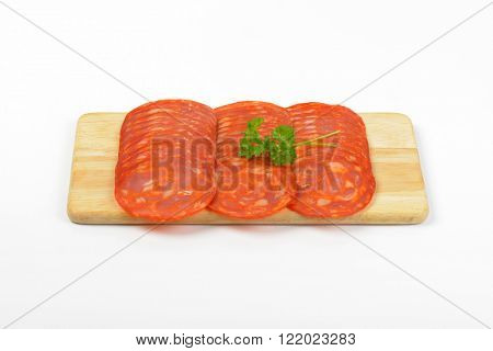 slices of chorizo salami ranked on wooden cutting board