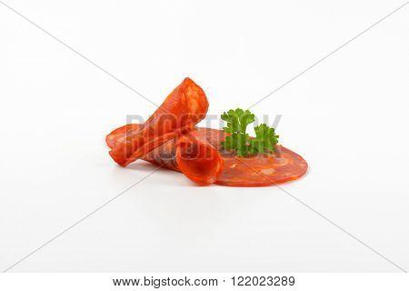 slices of chorizo salami with parsley on white background