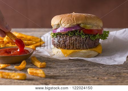 man dipping french fries in ketchup with cheeseburger off to the side on a rustic wood surface set against a brown backdrop