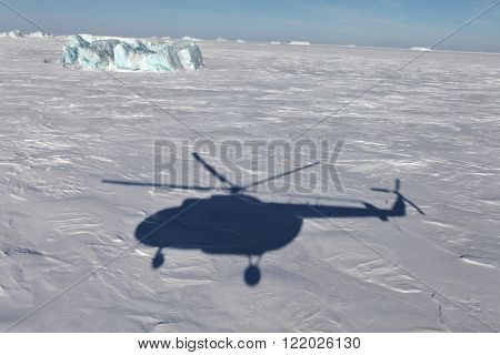 Aerial view of iceberg in frozen Arctic Ocean and helicopter shadow