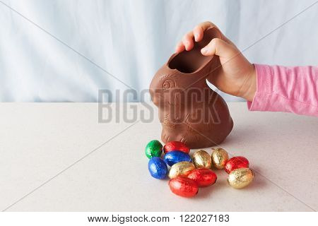 Child's hand breaking an ear off chocolate Easter bunny with copy space.