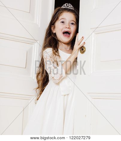 little cute girl at home, opening door well-dressed in white dress, adorable milk fairy teeth, curious child