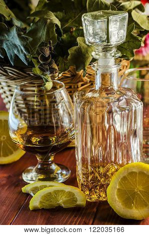cognac and a lemon on a background of oak leaves